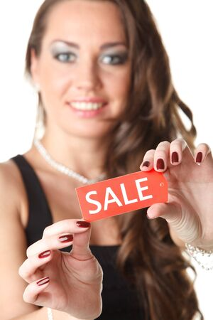 favourable: Beautiful young woman showing SALE sign on a white background. Selective focus on sign.