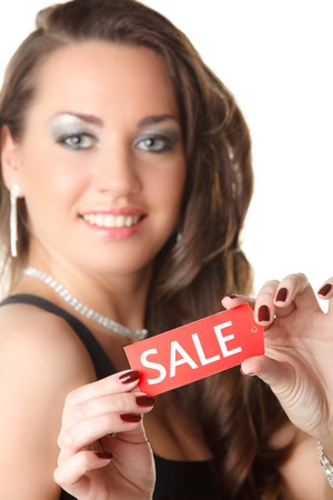 Beautiful young woman showing SALE sign on a white background. Selective focus on sign. photo