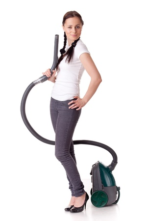 Young woman with vacuum cleaner on a white background. Housekeeping. photo