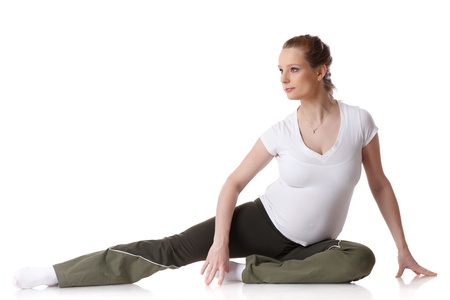The active pregnant woman does sports exercises on a white background. Care of health and pregnancy. Stock Photo
