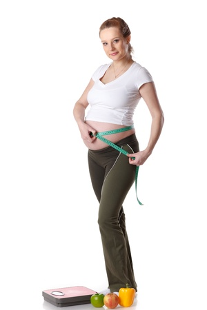 Young  pregnant woman with scales and fruit on a white background.  Concept of healthy lifestyle. photo