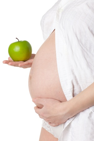 Pregnant woman with apple on a white background. photo