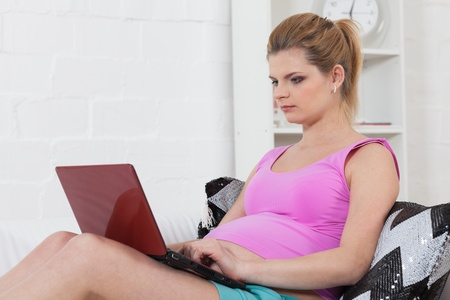 The beautiful young pregnant woman with laptop sits on the house sofa. photo