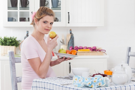 Beautiful pregnant woman with fresh fruit on the  house kitchen. Stock Photo - 13547497