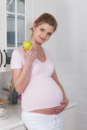 Beautiful pregnant woman with fresh apple on the  house kitchen. photo
