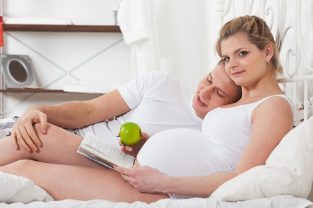 Happy pregnant family with book and apple lies on the house bed. photo