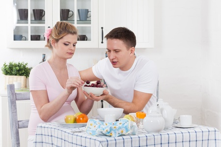 Happy pregnant family with fresh  fruit  on the  house kitchen. photo