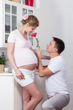 life giving birth: La mujer embarazada feliz con el marido en la cocina de la casa. Foto de archivo