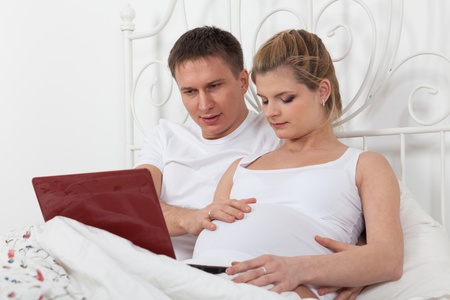 Happy pregnant family with notebook lies on the house bed. Stock Photo - 13547573