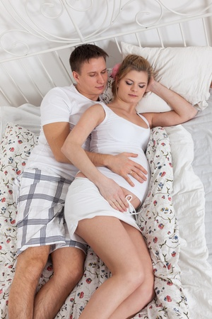 Happy pregnant family  lies on the house bed. Stock Photo - 13547615