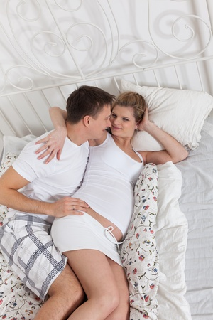 Happy pregnant family  lies on the house bed. Stock Photo - 13547614