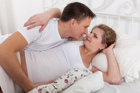 Happy pregnant family  lies on the house bed. Stock Photo - 13547583