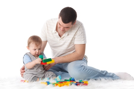 Father with small baby play on a white background. 免版税图像