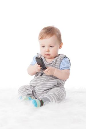 Zoete kleine baby met mobiele telefoon op een witte achtergrond. Stockfoto
