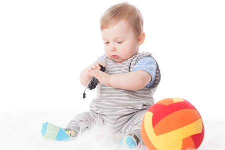 Sweet small baby with mobile phone on a white background. Stock Photo - 13670265