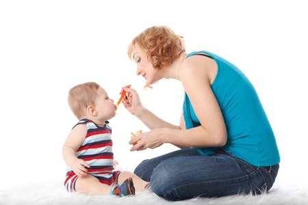 Young mother feeds  her baby on a white background. Happy family. photo