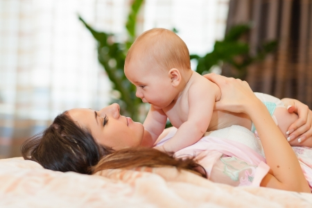 young diapers: Mother and  her sweet  baby in the room at home. Happy family. Stock Photo