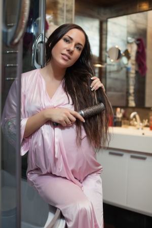 Young pregnant woman brushes long hair in a bathroom. Stock Photo - 13714187