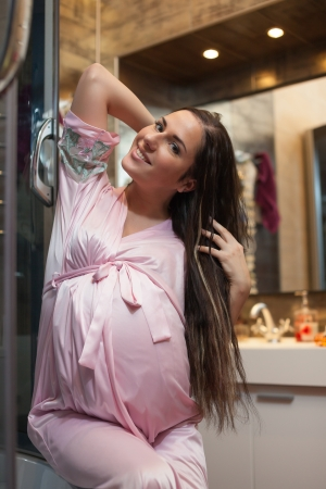 Young pregnant woman brushes long hair in a bathroom. photo