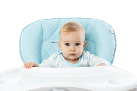 interrogatively: Sweet small girl sits in baby chair on a white background