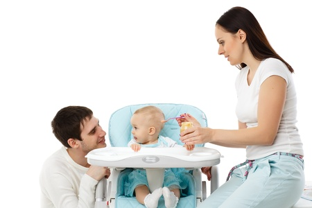 Young parents feed  baby on a white background  Happy family Stock Photo - 17412050