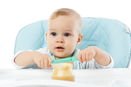 Sweet baby learning to eat with spoon sits on baby chair on a white background  Stock Photo - 17412062