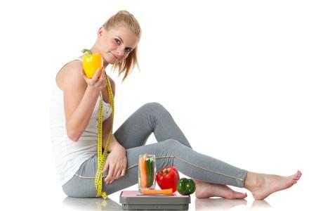 Sportieve jonge vrouw met schalen en groenten op een witte achtergrond. Concept van een gezonde levensstijl. Stockfoto