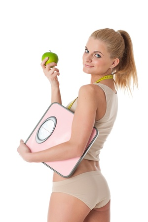 Sporty young woman with scales and apple on a white background.  Concept of healthy lifestyle. Stock Photo - 17405718