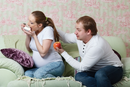 Pregnant family sit on a sofa at home with  an apple and cake. Concept of healthy food. photo