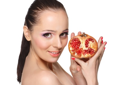 Portrait of a beautiful  young woman with pomegranate on a white background. photo