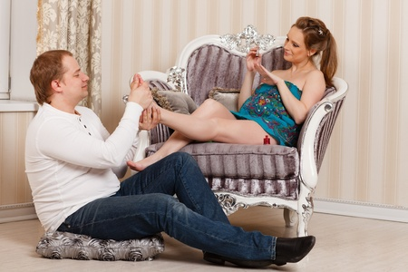 The husband does massage of feet of the pregnant wife of the house. Happy pregnant family. photo