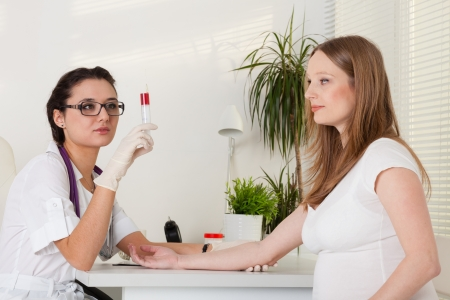 The doctor takes blood from a vein from the pregnant woman Stock Photo - 17817863