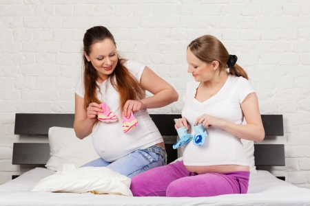 Two pregnant girlfriend  with childrens clothes sit on the bed at home. photo