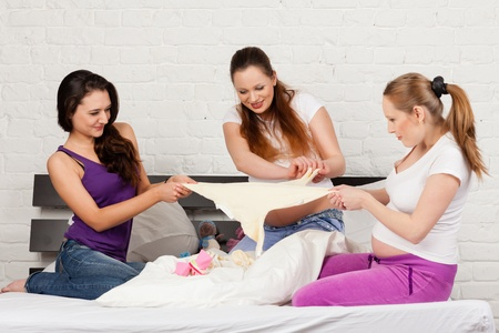 Three pregnant girlfriend  with children's clothes sit on the bed at home. Stock Photo - 17817868