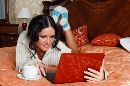 Young woman with laptop lies on the house bed. photo