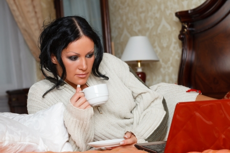 Young woman with laptop lies on the house bed. Stock Photo - 17893651