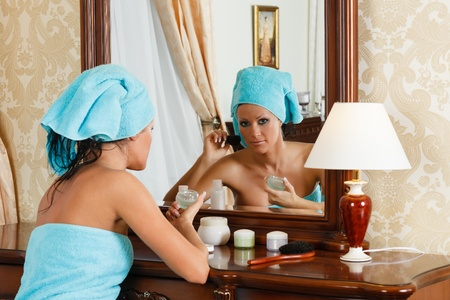 The young woman does a make-up, sitting before a house  dressing table. photo