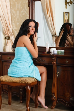 Young woman brushes hair, sitting before a house  dressing table. photo