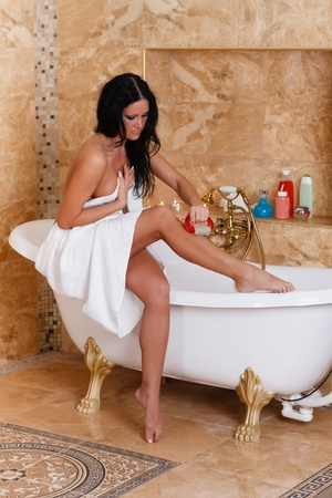 Young woman with a massager in a bathroom  Concept  of body care  Stock Photo