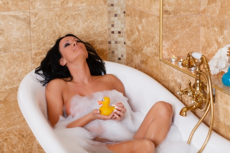 lying in bathtub: Young beautiful woman in a bathroom  Concept body care