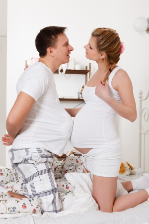 The happy pregnant woman with the husband sit on the house bed.
