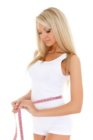 The beautiful young woman measures a volume of waist on a white background.  Concept of healthy lifestyle. photo