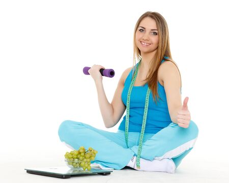 Young woman with scale, fresh grapes and dumbbells on a white background.  Concept of healthy lifestyle. photo