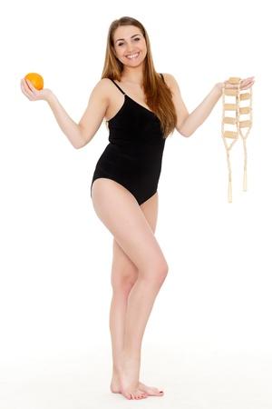 with orange and white body: Mujer joven con un masaje y una naranja sobre un fondo blanco. El concepto de cuidado del cuerpo.