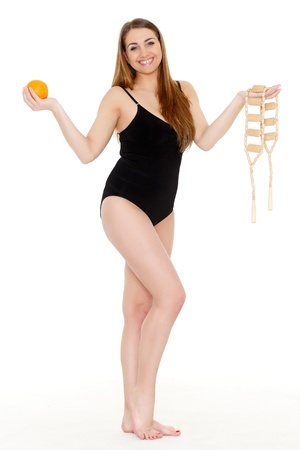 Young woman with a massager and an orange on a white background. Concept  of body care. Stock Photo - 18411930