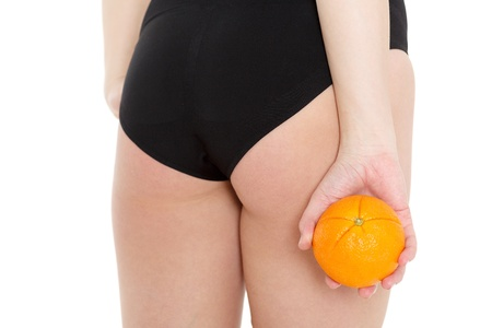 Hips of young woman with an orange on a white background. Concept  of body care. Stock Photo - 18411974