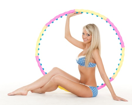 Young sporty woman with a hula-hoop on a white background.  Fitness. photo