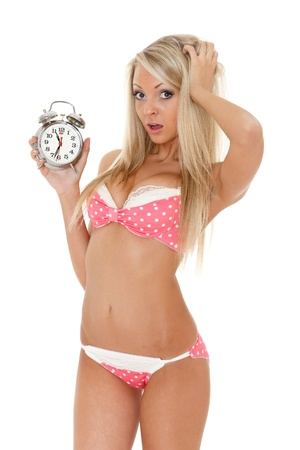overslept: Unhappy young woman with horror looks at an alarm clock on a white background. Has overslept. Stock Photo