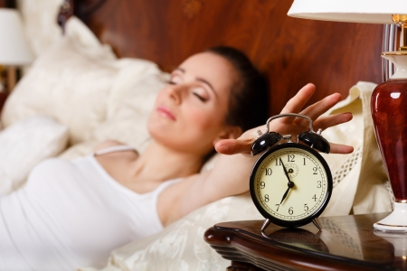 awaking: Young sleeping woman and alarm clock in the bedroom.  Selective focus on a alarm clock. Stock Photo