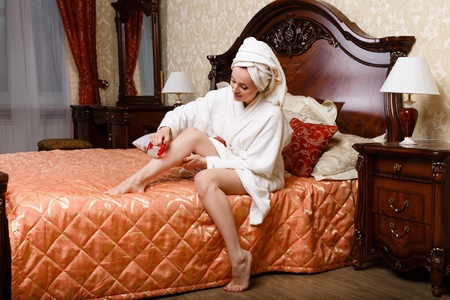 Young woman with a massager in a bedroom. Concept  of body care. Stock Photo - 19356384